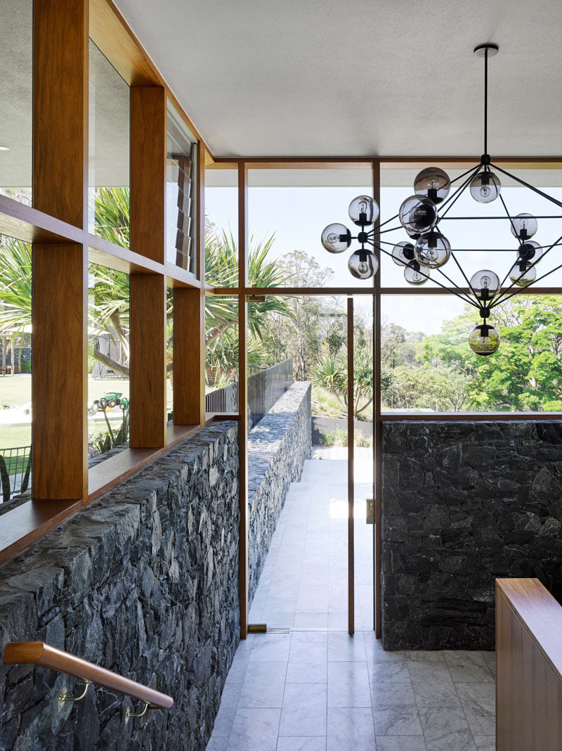 Carrara marble has been used as flooring throughout the home, and wood frames surround the windows. in this modern house.