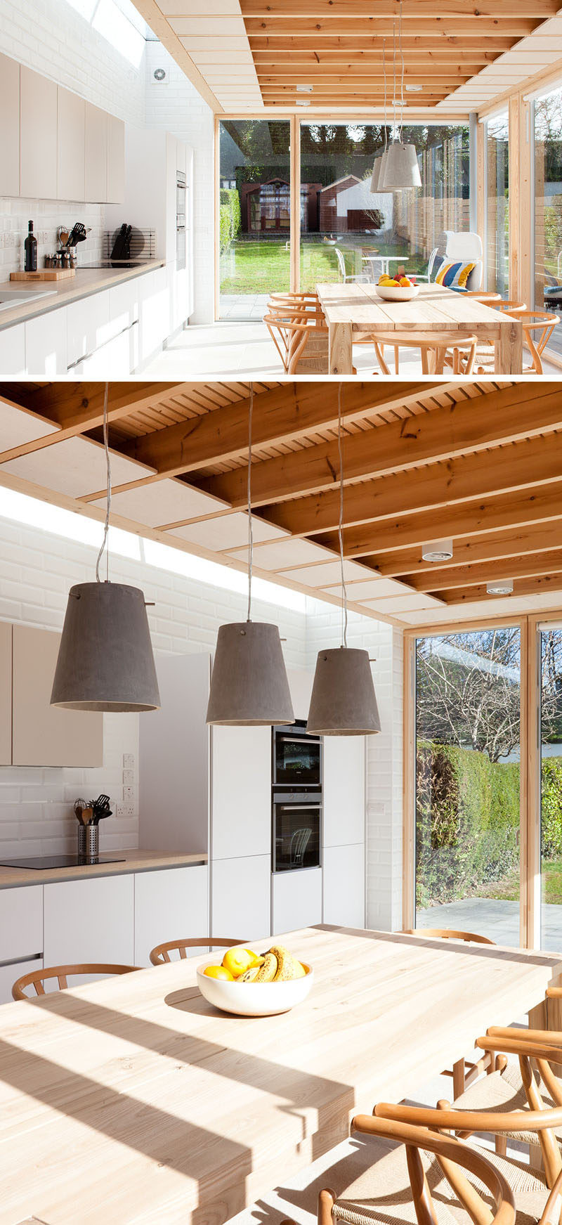 This modern house extension includes a dining table and a kitchen. Three concrete pendant lights anchor the dining table and chairs in the room.