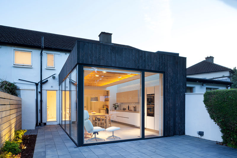 This modern house extension is covered in charred timber while the interior is a bright and airy space with a kitchen, a dining area and plenty of windows.