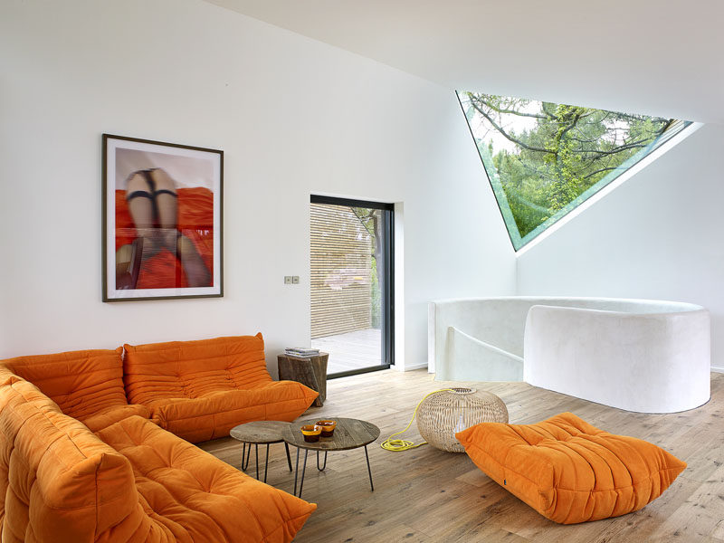 In this modern living room, the bright orange couch creates a comfortable spot to sit, while a triangular window provides a unique view of the trees.