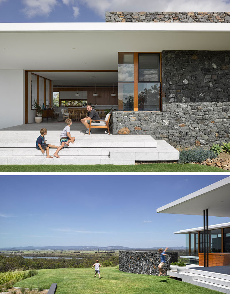 This modern house features a covered outdoor area with steps that lead down to the grassy backyard.