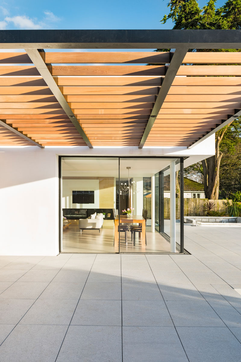 This modern house has a wood pergola that provides shade on a sunny day.