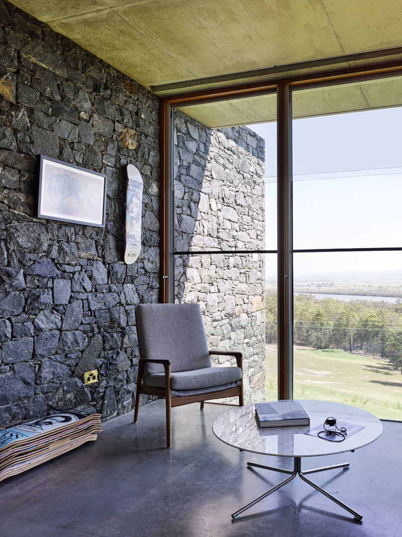 Large windows frame the picturesque views of the landscape from this modern house, while the bluestone walls travel from the exterior of the house, through to the interior.