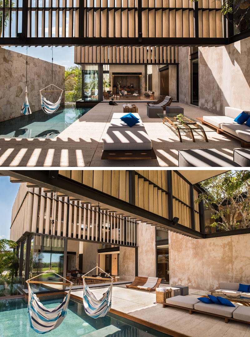 Two hammocks hang above this modern swimming pool, while a stone wall creates privacy for those swimming.