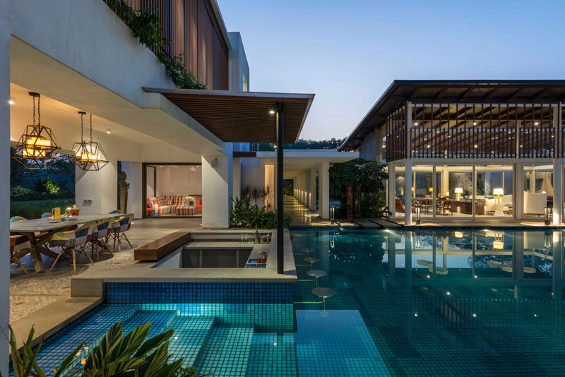 This modern house has a large swimming pool, a swim-up bar and an outdoor dining area.
