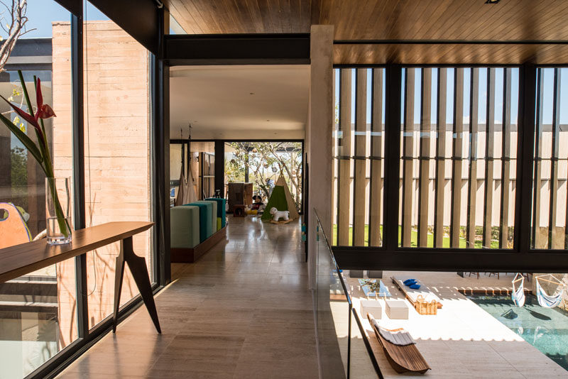 This modern house has a small bridge that looks down to the courtyard on the left, and on the right, it looks down to the outdoor entertaining area and pool.