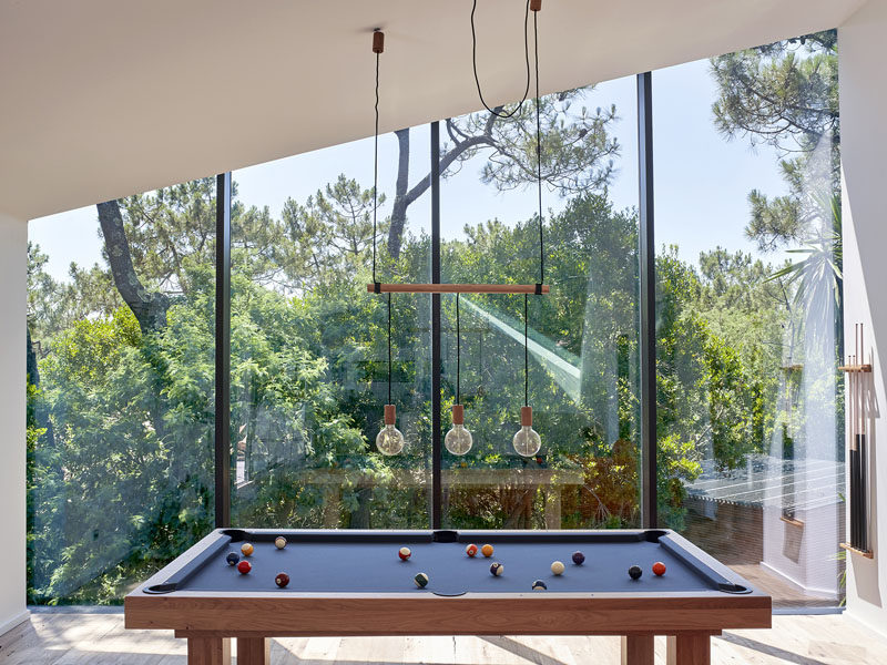 Large floor-to-ceiling windows follow the line of the roof in the games room of this modern holiday house.