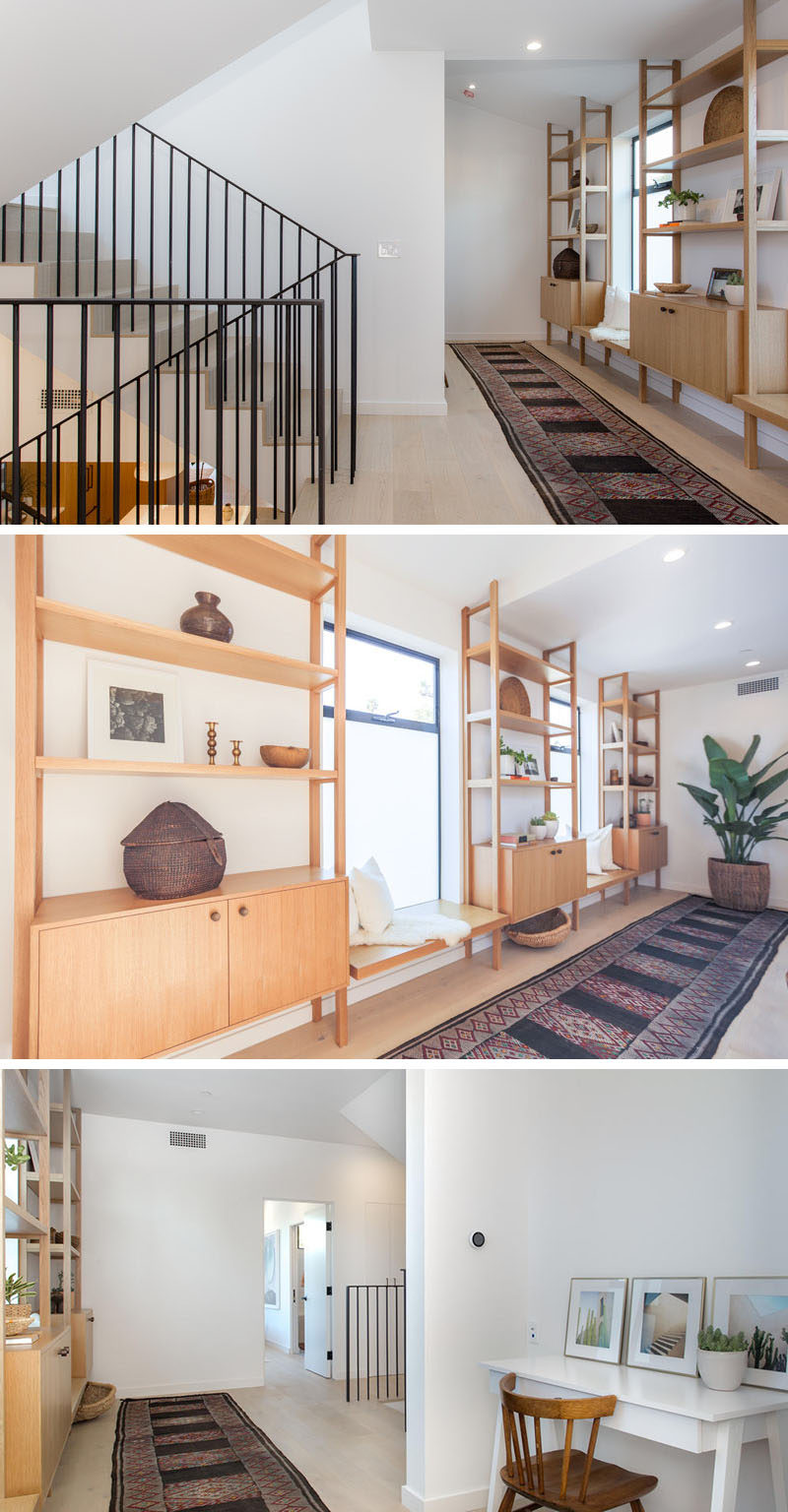 Wide oak flooring covers the upper floors of this modern house, and wood shelving provides the perfect spot for displaying personal items or for sitting and looking out the window.