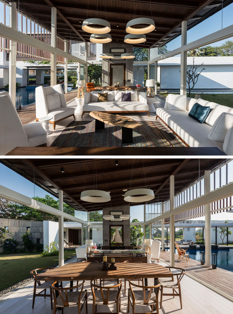 The main living and dining area of this modern house has walls of sliding glass doors, with one side opening up to the pool and on the other side, a manicured lawn.