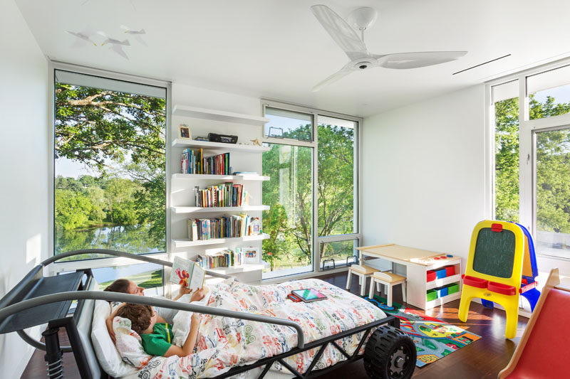 In this boy's bedroom, floor-to-ceiling windows provide views of the treetops, while a car inspired bed creates a sense of fun.