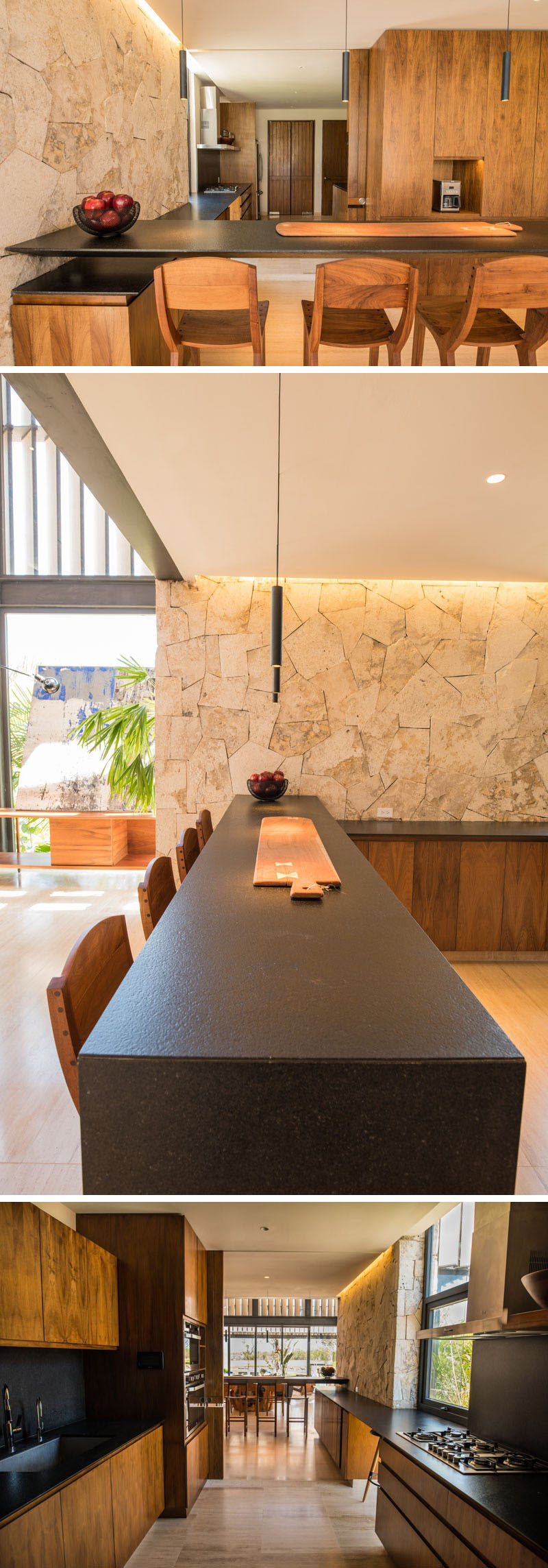 This modern kitchen features a light stone wall with a contrasting dark countertops and wood cabinetry.