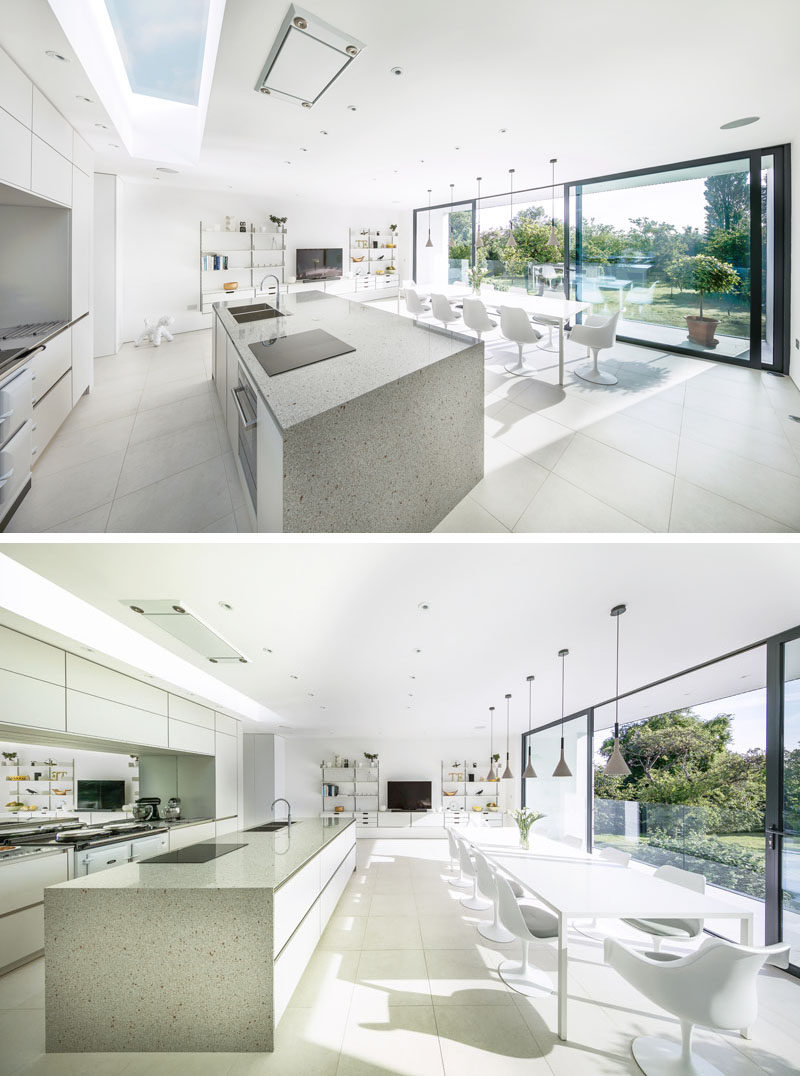 This kitchen and dining area, which are located in a cantilevered portion of this modern house, are filled with natural light from the large sliding glass doors and a skylight above the kitchen.