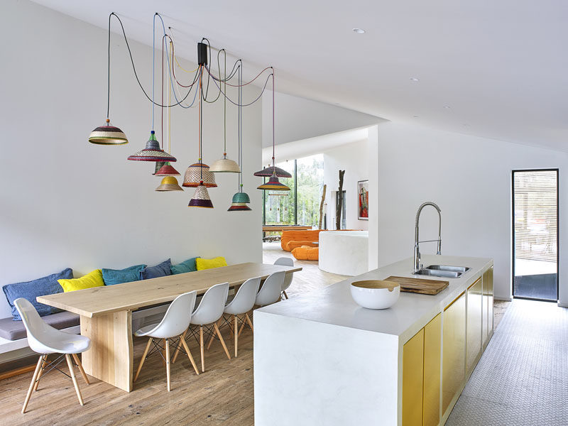 In this modern holiday house, the dining area and kitchen share the same room. The large dining table is anchored in the room by a collection of colorful pendant lights hanging from the ceiling. In the kitchen the cabinets have a gold metallic front, adding to the touch of color in the white space.
