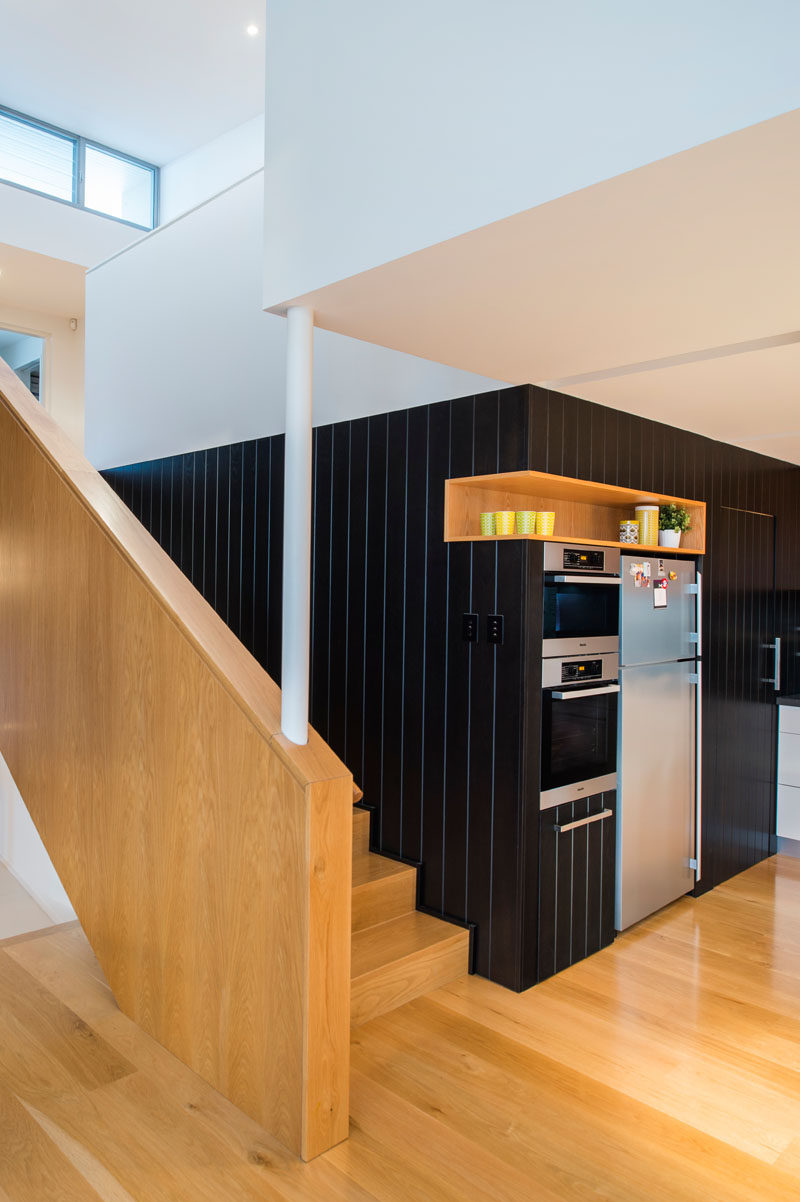 In this modern kitchen, a black accent wall is broken up by the use of a single wood shelf that's built into the wall and sits above the fridge.
