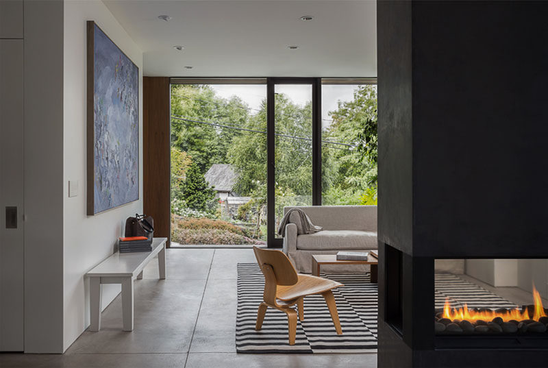 This modern house interior features a double-sided fireplace that can be enjoyed from both the dining room and the living room, while a large window provides views of the street and a nearby park.