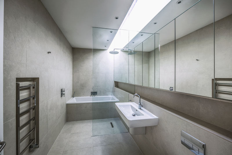 A skylight has been installed in this modern bathroom, creating a bright strip of natural light that brightens up the neutral color palette. A wall of mirrors runs the length of the room and a glass partition separates the wet areas from the rest of the bathroom.