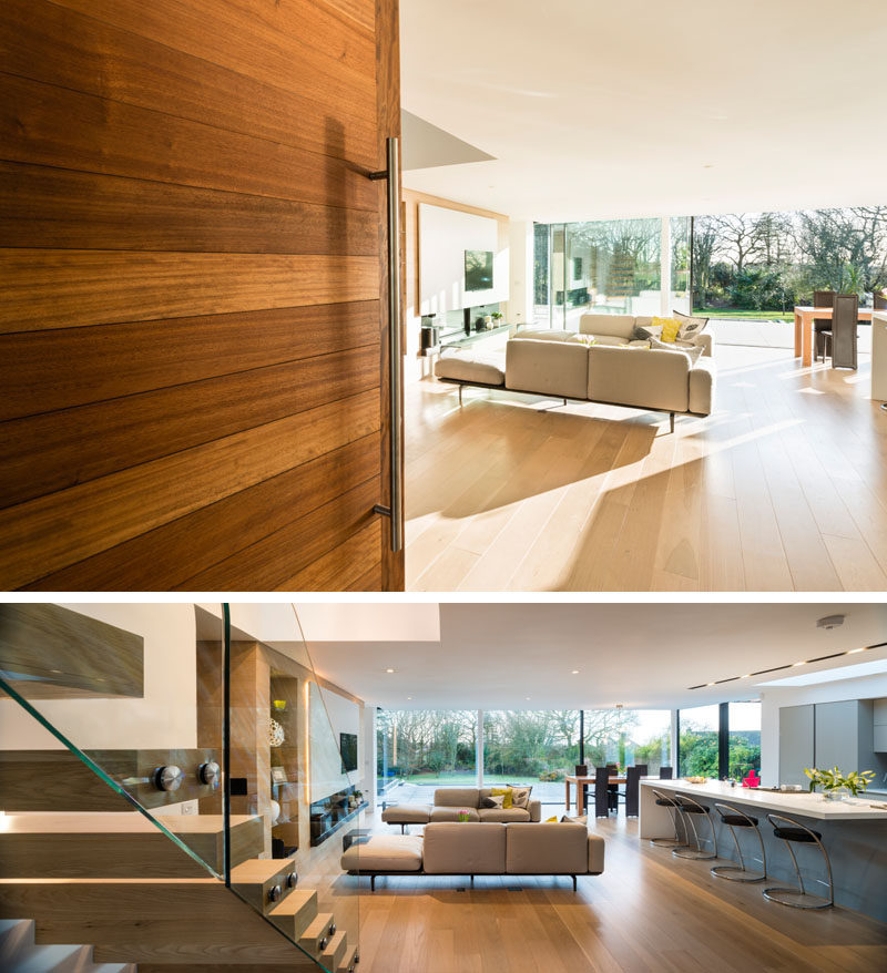 This large modern wood front door welcomes you into the bright interior of this modern house, that has an open floor plan on the main floor.