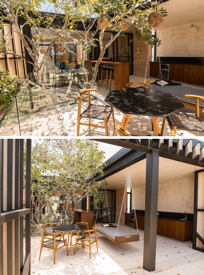 This modern house has a partially covered outdoor entertaining area on the upper floor of the home. There's a kitchen, a bar, a swing, and a dining area.