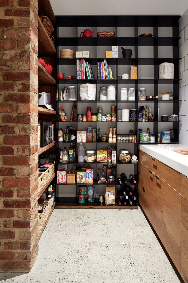 This modern pantry has open black steel shelving as well as recycled wood shelving. Polished concrete floors are used throughout the main floor of the home.