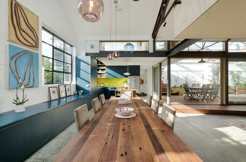 In this modern converted warehouse, custom blue cabinetry runs along the wall and into the kitchen, while a large wood dining table is anchored in the space by colorful glass pendant lights.
