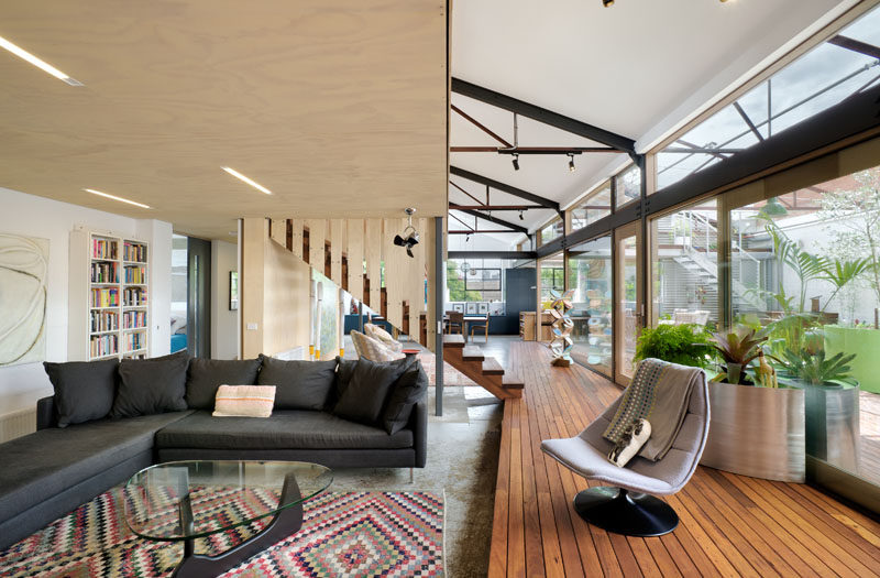 In this modern converted warehouse, the living room is stepped down from the wood deck. Simple lighting has been embedded into the wood ceiling.