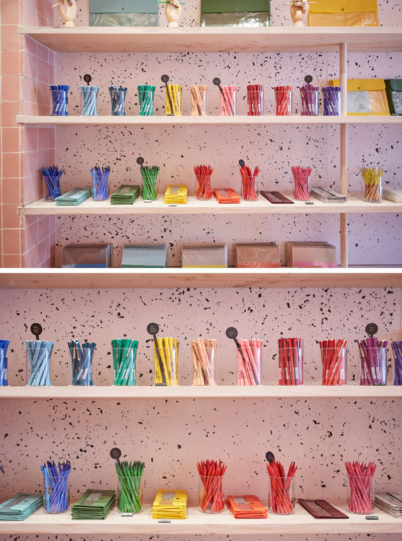 In this modern retail store, wood shelving has been used and embedded slightly into the tiled wall, while dowels support the shelves, and on the wall the jesmonite, with its freckled black and pink pigment, creates a unique backdrop for the colorful pens.
