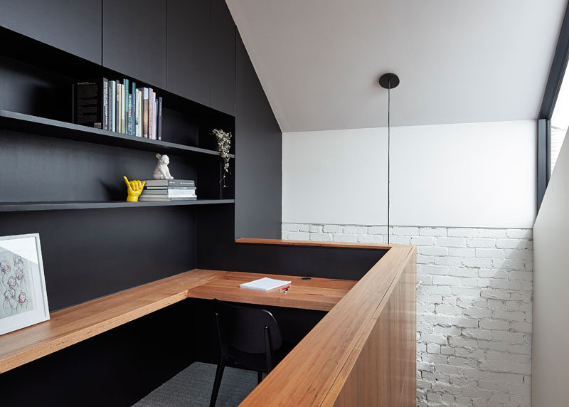 This modern home office features a built-in wood desk and black open shelving.