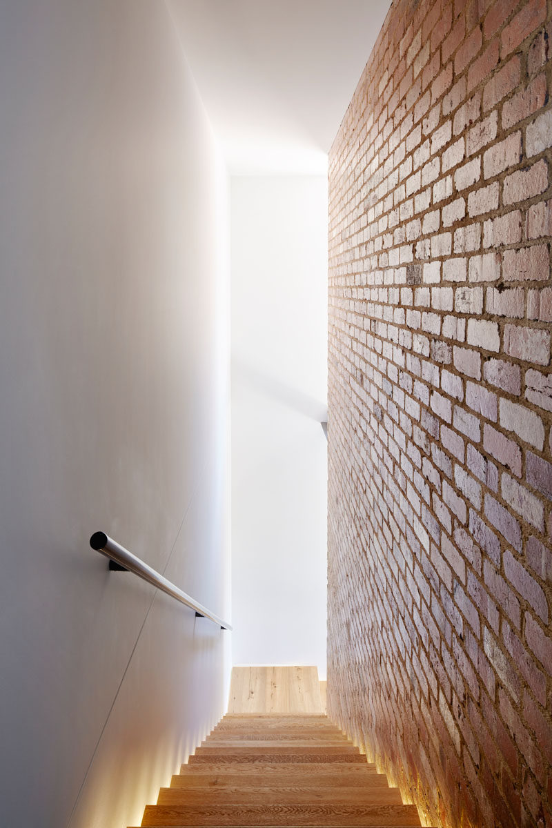 Wood stairs, sandwiched between a white wall and a brick wall, are lit up with hidden lighting on either side.
