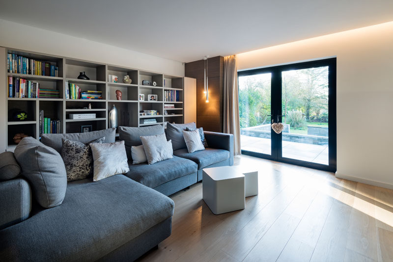 This modern house has a tv room with a large sofa and plenty of shelves for storing books and games.