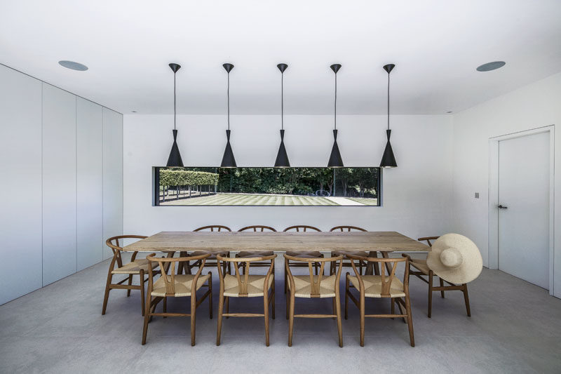 In this modern and formal dining room, five black pendant lights hang above wood table and chairs, while a large horizontal window perfectly frames the garden.