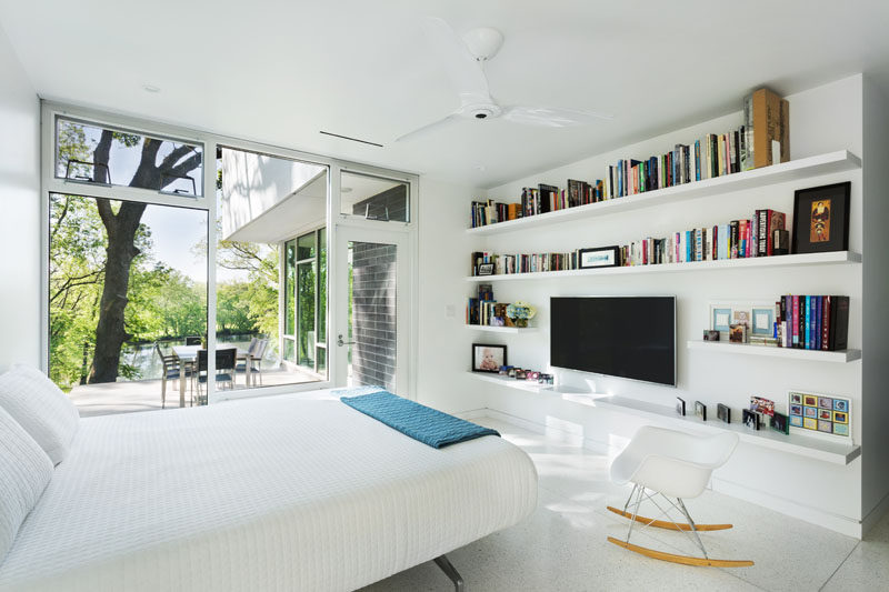 This modern master bedroom is located on the main floor of the home, with a wall of floating shelves surrounding a television. There's also access to the patio that sits off to the side of the living room.