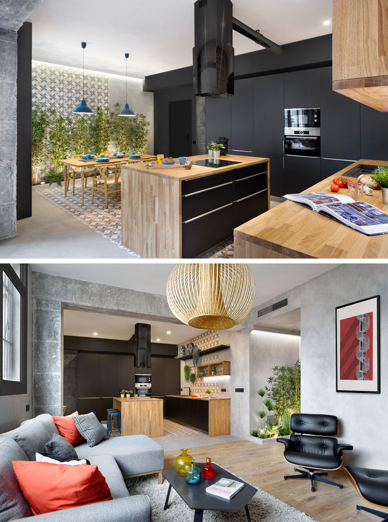 The kitchen in this modern apartment combines matte black and wood cabinets for a contemporary appearance. The use of plants adds a natural touch throughout the apartment.
