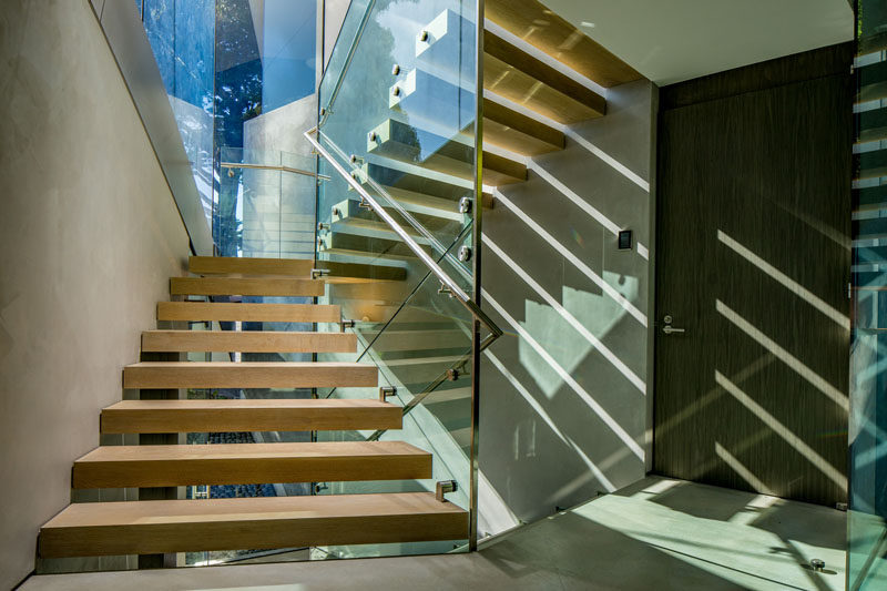 The stairs in this modern house have limed white oak treads with an oil finish, and throughout the house, the flooring is polished concrete.