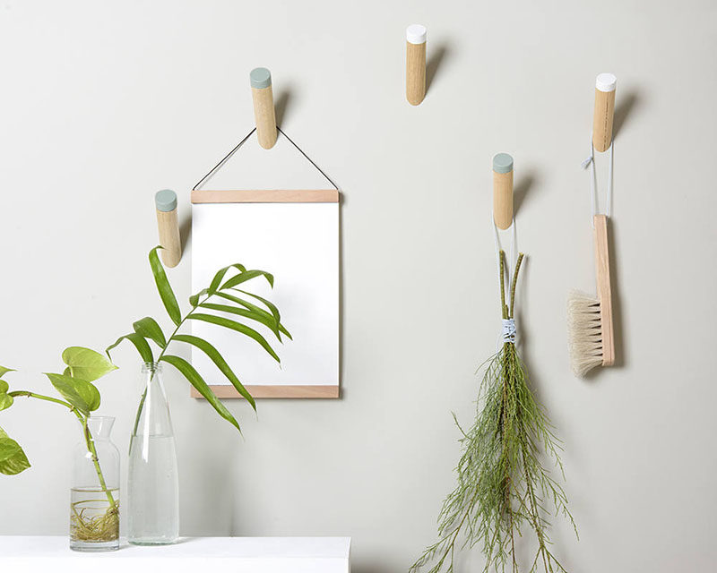 Simple dowel wall hooks with colored tips add a soft pop of color to otherwise plain walls.