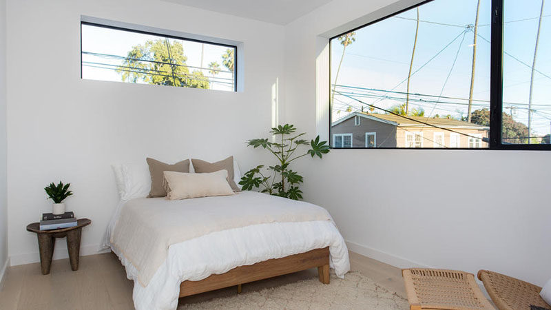 This modern bedroom is simple in its design, with white walls and wide oak flooring.