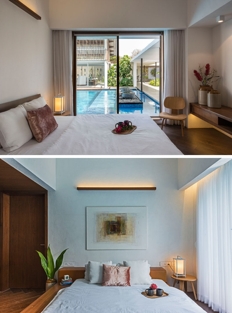 In this poolside modern bedroom, a simple wood light fixture adorns the wall, while a sliding glass door allows natural light and the breeze to enter the room.