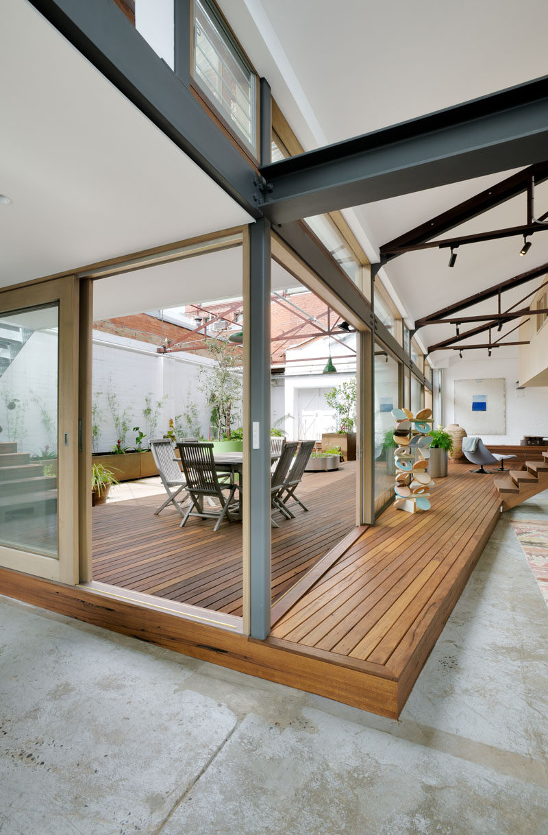 In this modern converted warehouse, a new raised wood deck connects the living areas of the home with the courtyard. Sliding glass doors and windows allow the sunlight to filter through to the interior.