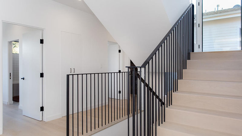 The stairs that connect the various levels of this modern house feature the same wide oak on the treads as the flooring, and black handrails tie in with the black door hardware.