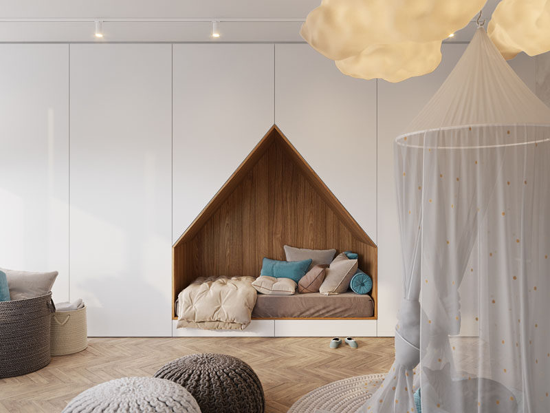 This modern bedroom design has a bed that's been built into a wall of floor-to-ceiling white cabinets, freeing up space to allow a large desk to sit under the window.