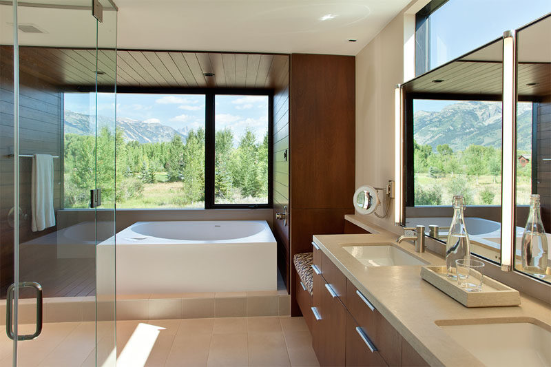 In this modern bathroom, multiple windows allow for plenty of natural light to fill the room, while the bathtub is surrounded by wood that wraps around from one wall to the other.