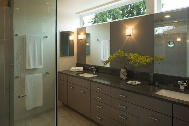In this contemporary master bathroom, a large vanity with dual sinks runs the length of the room and a glass shower surround keeps the room feeling bright and airy.