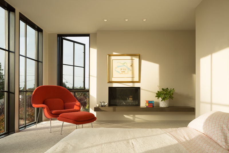 In this contemporary master bedroom, large grid windows provide plenty of natural light and fireplace make the room feel cozy, while the rest of the room has been kept neutral except for a bright Womb chair and ottoman.