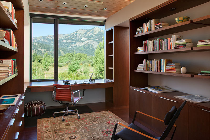 This modern home office features custom wood shelving that lines the walls and a desk has been positioned in front of the window to take advantage of the views.