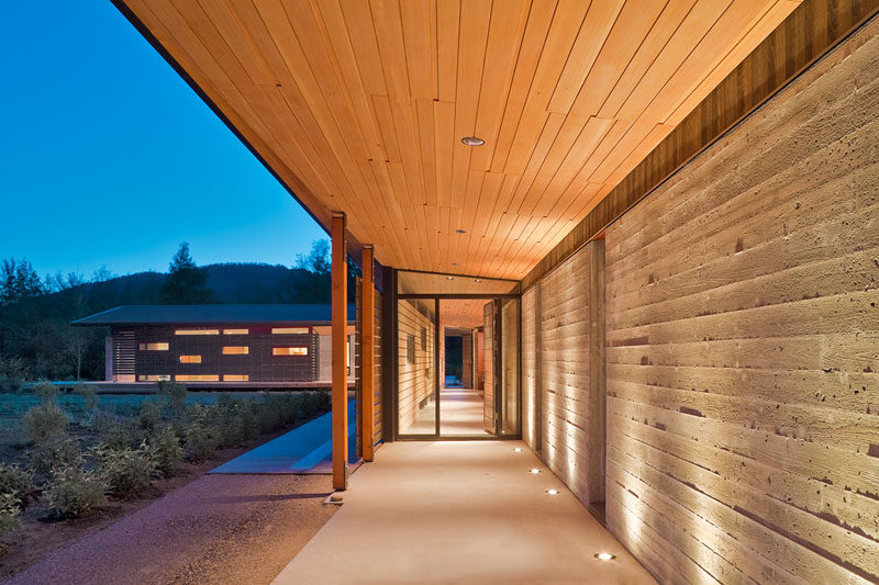 A board formed concrete wall highlighted by lighting and a wood overhang guide you to the front door of this modern mountain house.