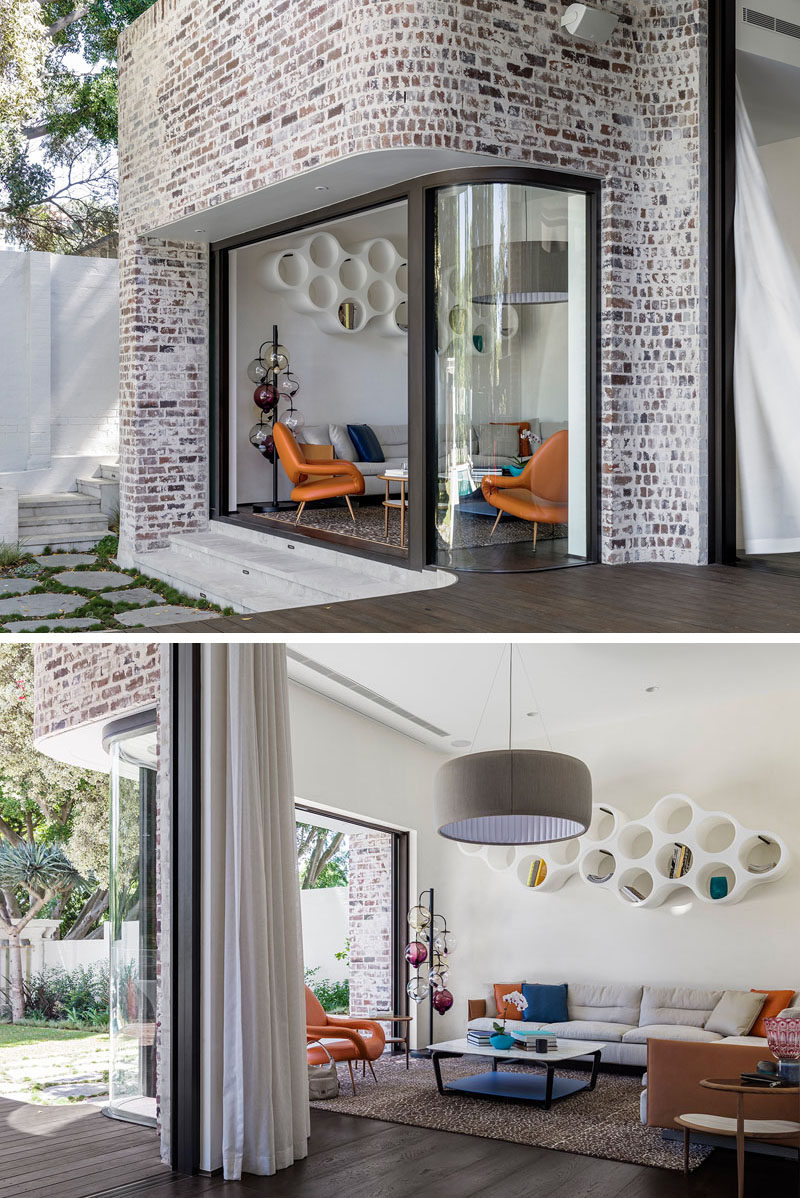 This modern house features a curved window and a sliding glass door surrounded by recycled brick, opens up the living room to the backyard.