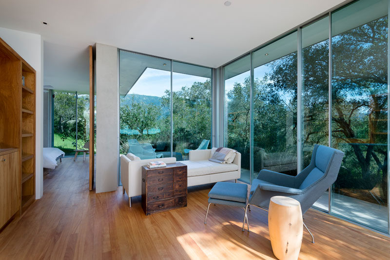 Floor-to-ceiling glass walls provides views of the surrounding landscape from this modern guest house.