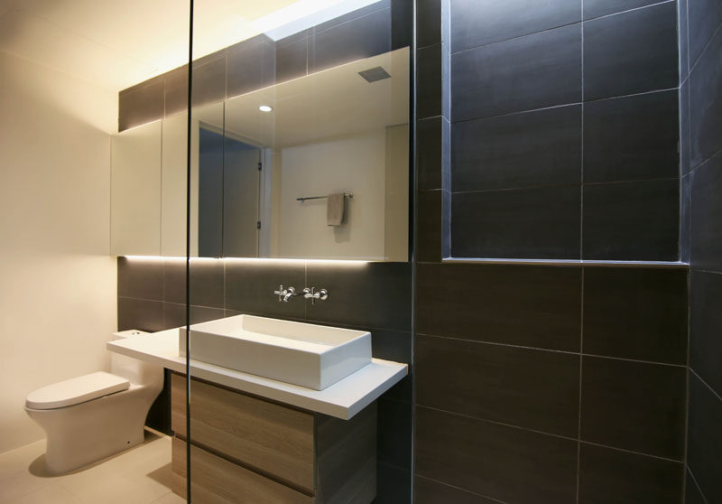 This modern bathroom uses dark tiles as an accent wall, while backlit mirror provides ambient light in the room. #ModernBathroom #tiles #bathroom