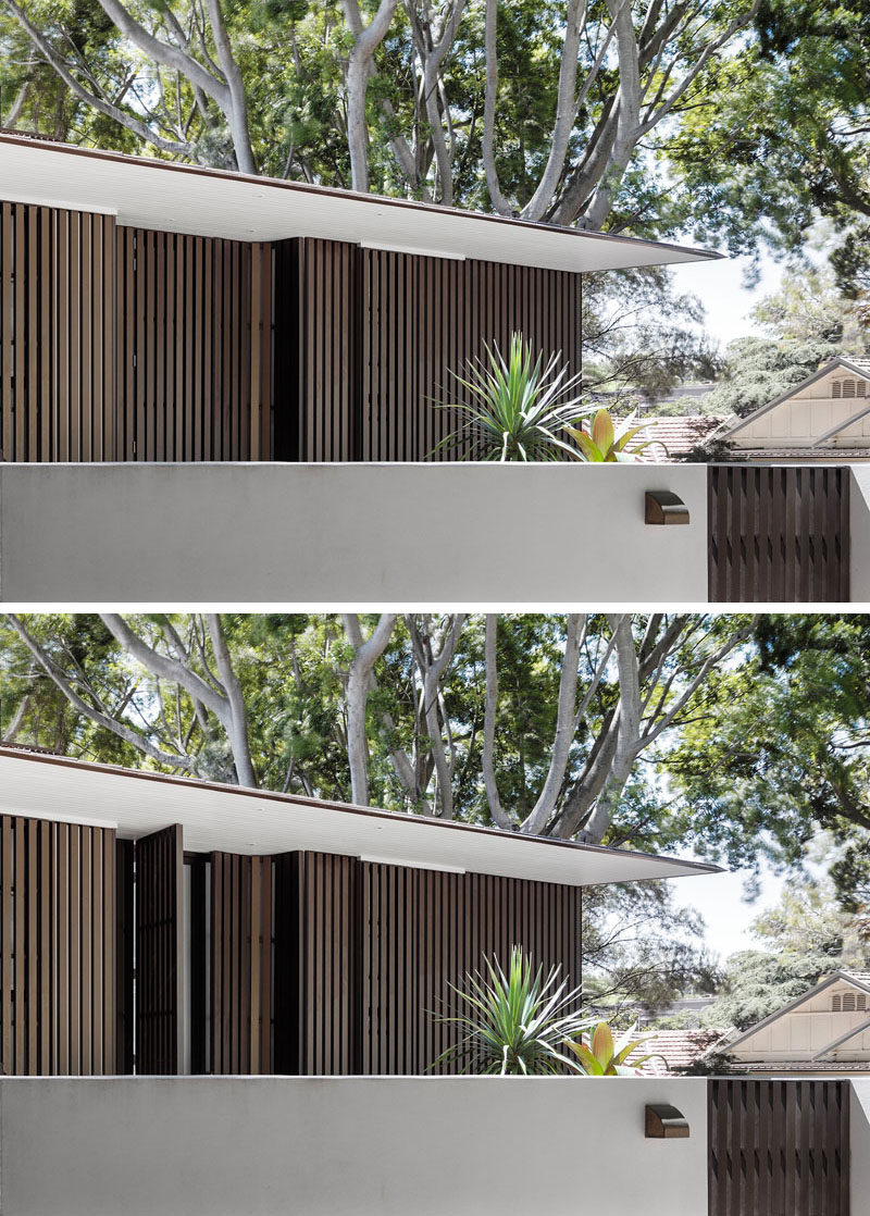 This modern house has a zinc roof that conceals gutters and down-pipes, creating a crisp exterior profile. The front door is hidden away from view within the anodized aluminum battens.