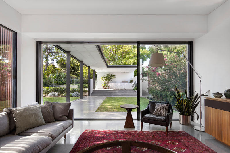 Concrete floors have been paired with white walls and black window / door frames to create a clean and modern aesthetic. The new living room opens up to the landscaped backyard through a large sliding glass door.