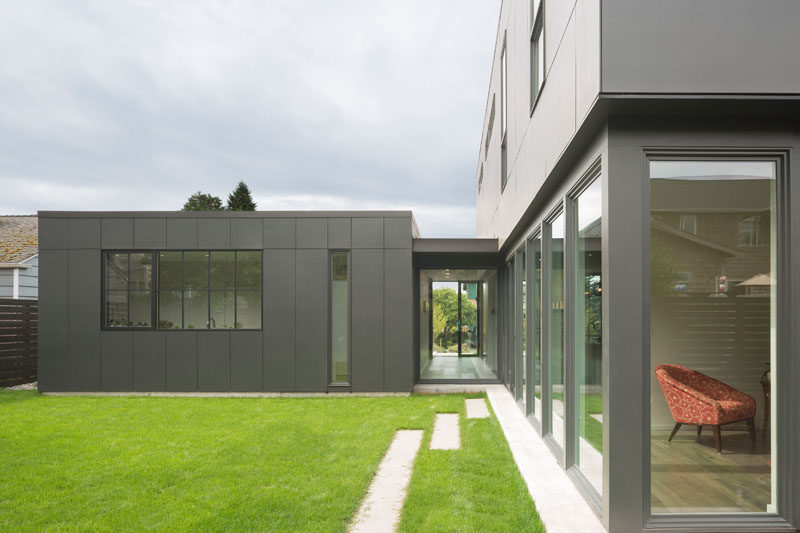 Sliding doors in the kitchen of this modern house open up to the grassy backyard. The backyard has a view of the laundry behind the garage and also a small media room, that's located next to the kitchen.